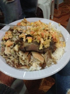 a plastic plate piled high with rice, beans, and meat