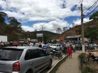 cars parked along the road and people gathered to hear Lula speak
