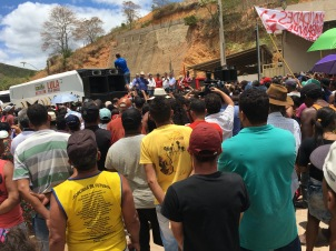 Lula speaks to a crowd of people from a podium by a parked bus